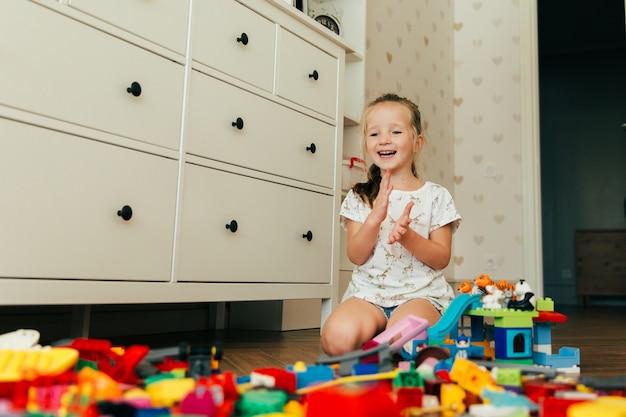Kleines glückliches mädchen, das mit bunten bauklötzen spielt. pädagogisches und kreatives spielzeug und spiele für kleine kinder. spielzeit und chaos im kinderzimmer