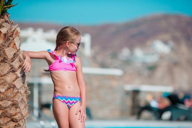 Kleines glückliches mädchen genießen ferien nahe swimmingpool im freien