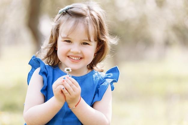 Kleines glückliches mädchen in einem blauen kleid spielt mit blumen