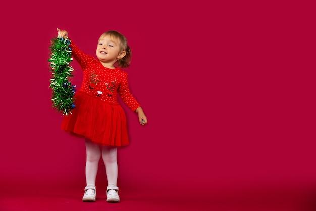 Kleines glückliches mädchen in einem roten neujahrskleid, mit einer grünen flauschigen girlande in ihren händen. urlaubskonzept an der roten wand.