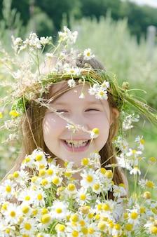 Kleines glückliches mädchen in einer girlande des feldes blüht in der wiese