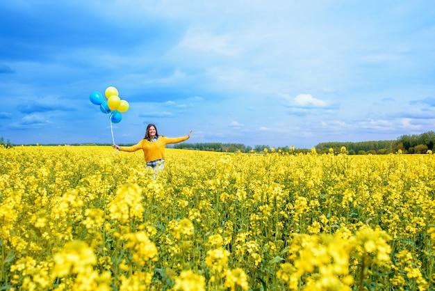 Kleines glückliches mädchen mit blau und gelb. gelbes rapsfeld. glücklich laufende kinder. konzeptfreiheit, sommer. raps ist eine alternative energie.