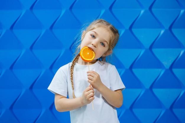 Kleines glückliches mädchen mit einer orange in der hand, schaut in die kamera gekleidet in weißem t-shirt, isoliert auf blauem hintergrund, kopierraum,