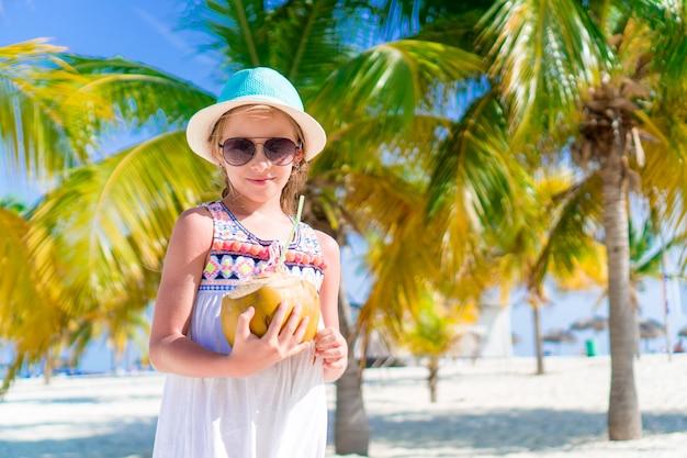 Kleines glückliches mädchen mit großen kokosnuss am strand