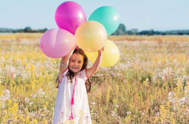 Kleines glückliches mädchen mit luftballons im freien