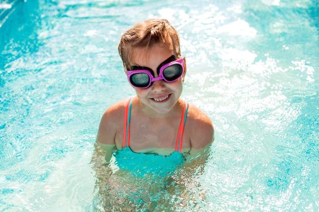 Kleines glückliches mädchen schwimmt im pool. sommerferien. mädchen in badeanzug und schwimmbrille.
