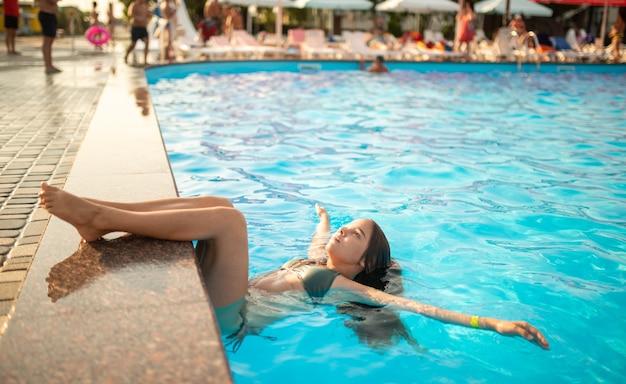 Kleines glückliches teenager-mädchen legt ihre beine auf den rand des swimmingpools