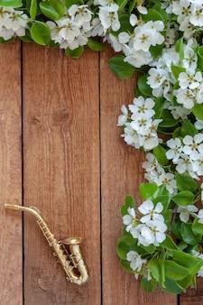 Kleines goldenes saxophon und blühende apfelbaumaste.