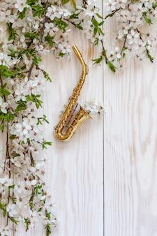 Kleines goldenes saxophon und blühende kirschbaumaste.