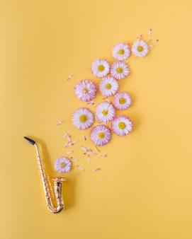 Kleines goldenes saxophon und rosa gänseblümchen auf orange hintergrund. postkartenkonzept