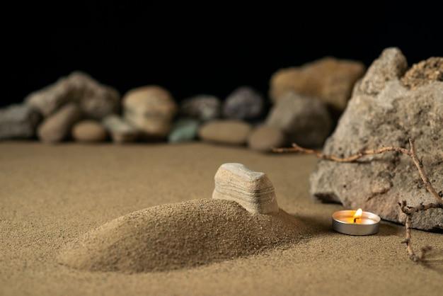 Kleines grab mit kerze und steinen auf sandbestattungskrieg