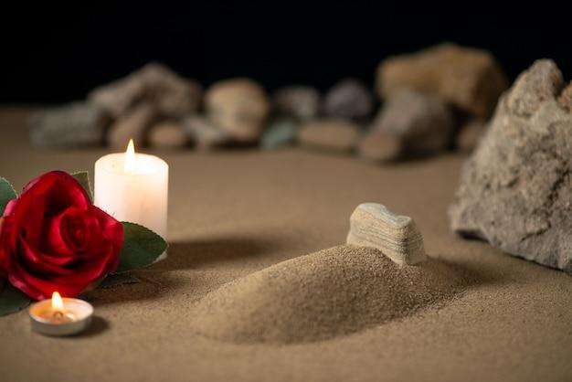 Kleines grab mit kerze und steinen auf sandbestattungskriegsmond