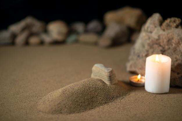 Kleines grab mit kerze und steinen auf sandbestattungskriegstod