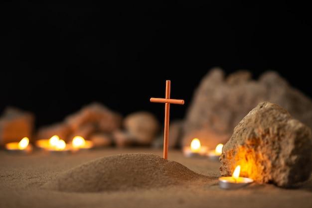 Kleines grab mit steinen und brennenden kerzen auf dunkler oberfläche