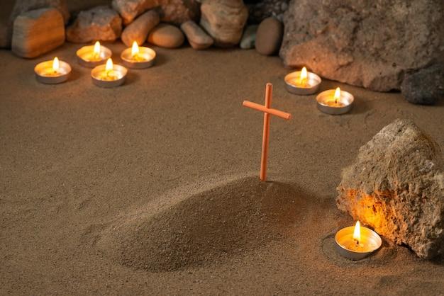 Kleines grab mit steinen und brennenden kerzen auf sandbestattungstod