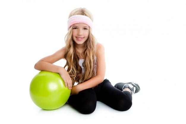 Kleines gymnastikmädchen der kinder mit grüner yogakugel