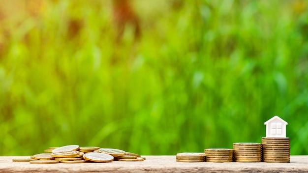 Kleines haus auf stapel goldenen münzen im garten. - konzept der als finanzinvestition gehaltenen immobilien.