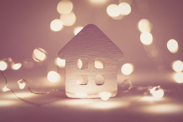 Kleines haus mit weihnachtsgirlande beleuchtet winterferienhintergrund