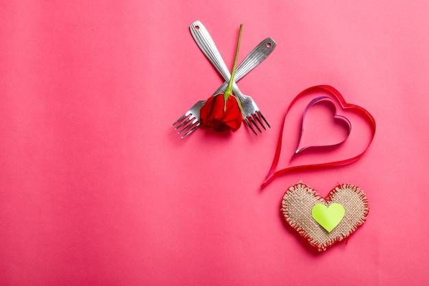 Kleines herz, rote rosenblüte und gabeln. romantisches abendessen für valentinstagkonzept