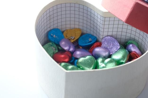 Kleines herzformgeschenk mit süßigkeiten auf weiß lokalisiert.