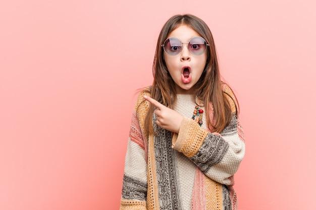 Kleines hippiemädchen, das auf die seite zeigt