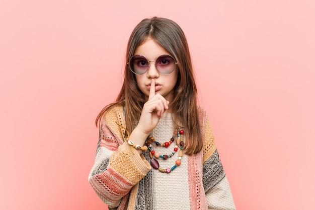 Kleines hippiemädchen, das ein geheimnis hält oder um ruhe bittet.