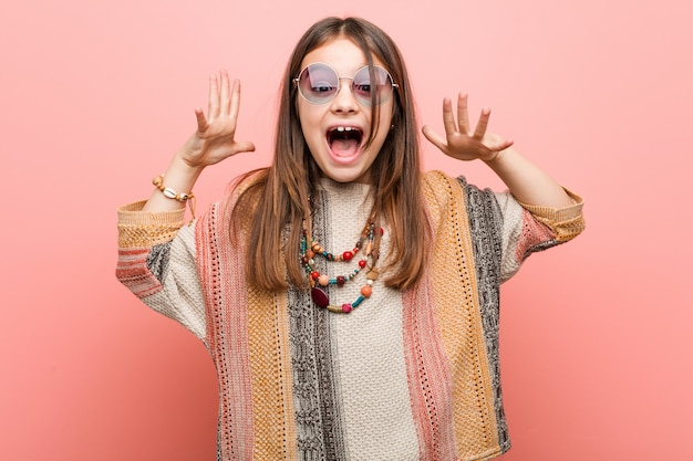 Kleines hippiemädchen, das einen sieg oder einen erfolg feiert