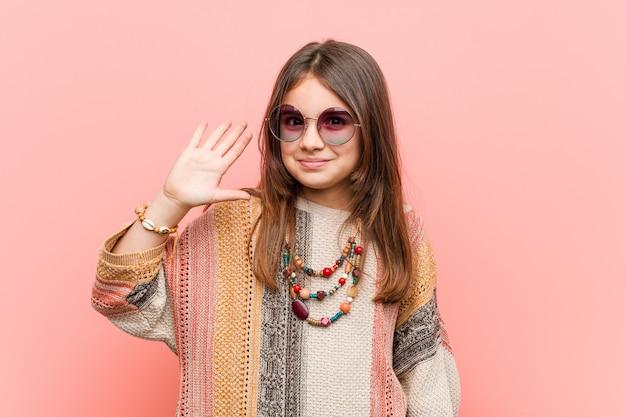 Kleines hippiemädchen, das freundliche darstellende nr. fünf mit den fingern lächelt.