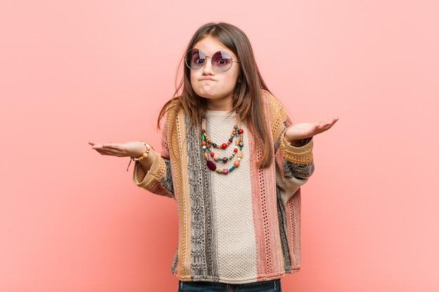 Kleines hippiemädchen, das seine schultern in fragender geste bezweifelt und zuckt.