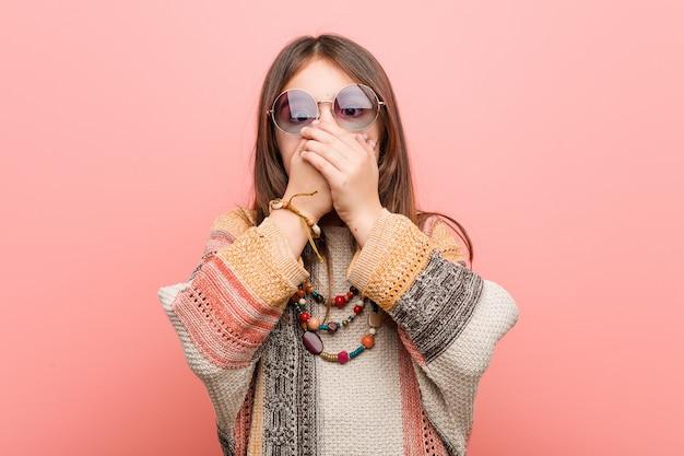 Kleines hippiemädchen entsetzte bedeckungsmund mit den händen.