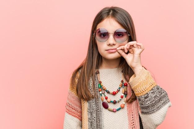 Kleines hippiemädchen mit den fingern auf den lippen, die ein geheimnis halten.