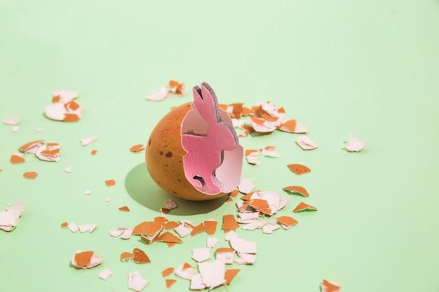 Kleines hölzernes kaninchen im defekten ei