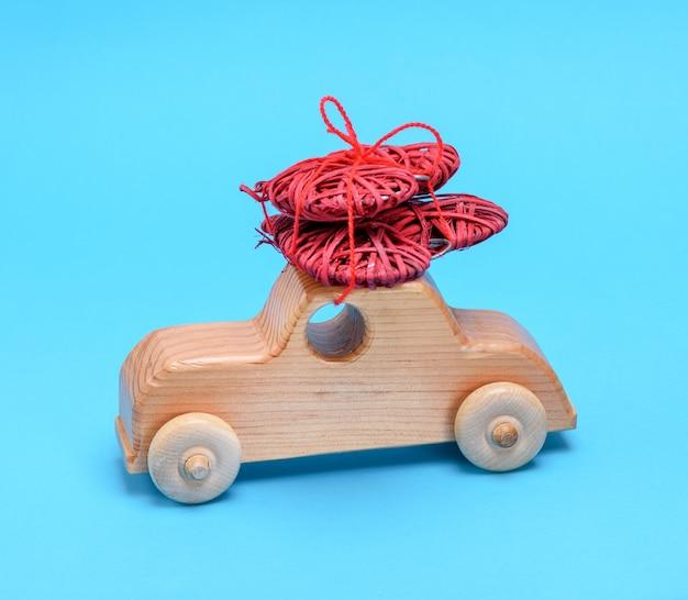 Kleines hölzernes kinderauto trägt ein geflochtenes rotes herz