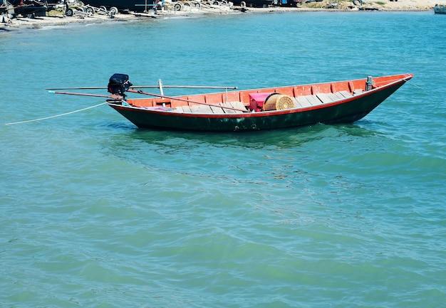 Kleines hölzernes motorboot, das auf blauem meer schwimmt