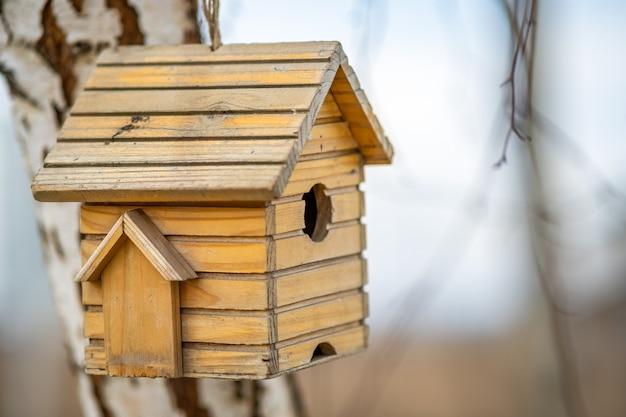 Kleines hölzernes vogelhaus, das an einem ast im freien hängt.