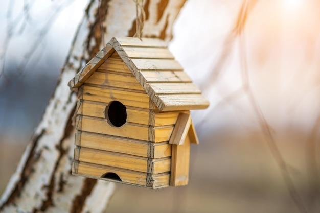 Kleines hölzernes vogelhaus, das draußen an einem baumast hängt.