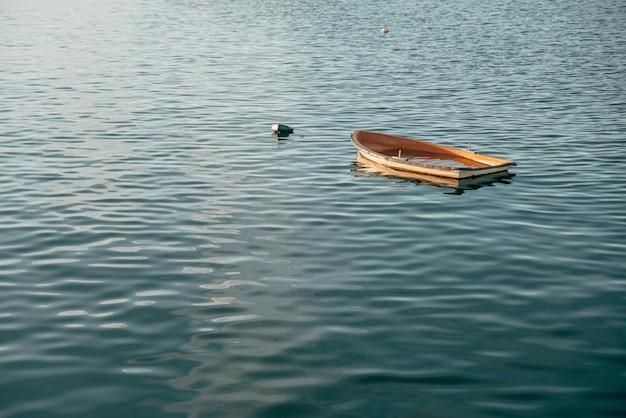 Kleines holzboot sinkt auf einem ruhigen see in pais vasco, spanien