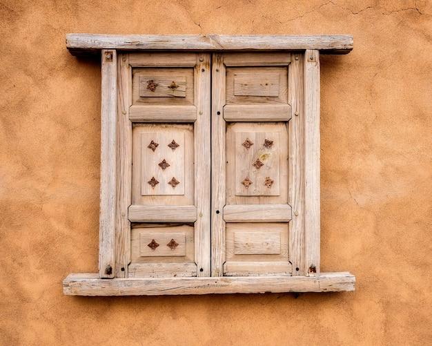Kleines holzfenster an einer orangefarbenen wand