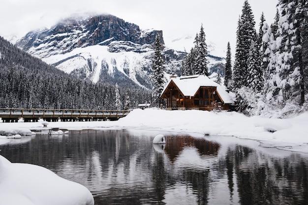 Kleines holzhaus bedeckt mit schnee nahe dem smaragdsee in kanada im winter