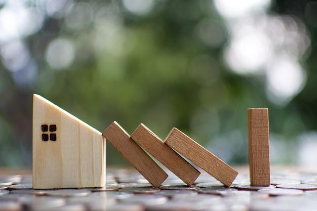 Kleines holzhausmodell auf planke beginnen, das wohn zu schützen.
