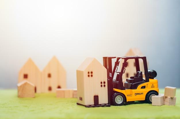 Kleines holzhausmodell mit gabelstapler für den umzug oder die renovierung von wohngebäuden für ein gutes gemeinschaftskonzept community