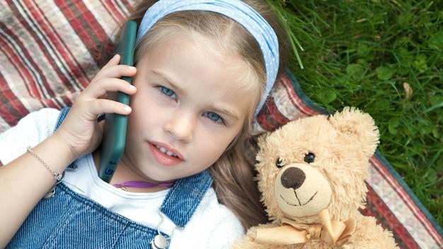 Kleines hübsches kindermädchen, das auf einer decke auf grünem rasen im sommer mit ihrem teddybärspielzeug liegt, das auf handy spricht.