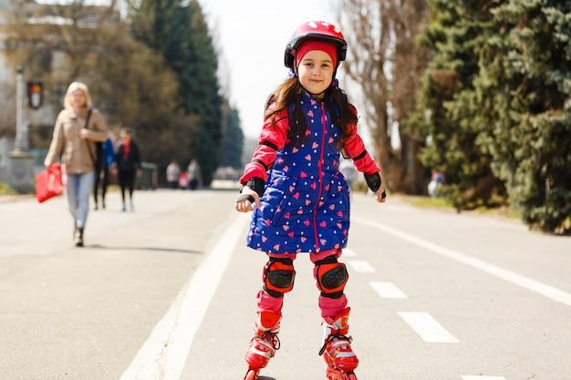 Kleines hübsches mädchen auf rollschuhen im sturzhelm an einem park