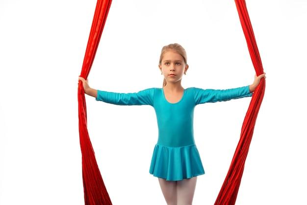 Kleines hübsches mädchen, das für leistung auf luftigen roten bändern auf einer weißen wand bereit macht. konzept der akrobatik und gute dehnung für kinder.