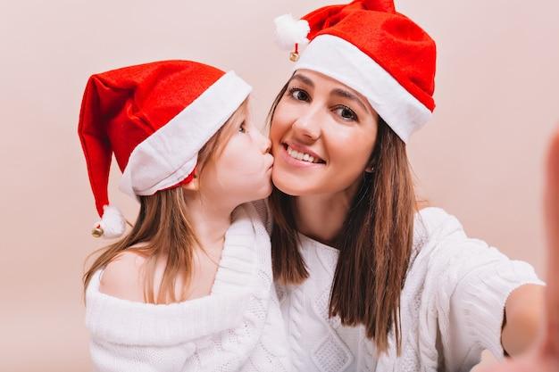 Kleines hübsches mädchen küsst ihre ältere schwester, die die ähnlichen weihnachtsmannhüte trägt, die frau, die selfie mit ihrer tochter auf isolierter wand macht, echte emotionen