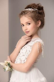 Kleines hübsches mädchen mit blumen in brautkleidern gekleidet