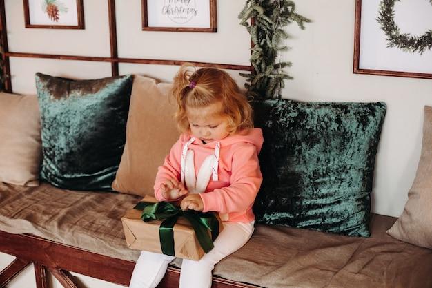 Kleines hübsches mädchen mit gewelltem haar sitzt auf dem sofa und öffnet eine schachtel mit einem geschenk