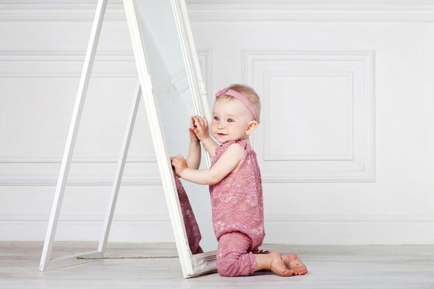 Kleines hübsches mädchen spielt mit einem großen spiegel