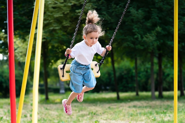 Kleines hübsches mädchen, süßes kind, kind schwingt bei sonnigem sommerwetter in einem park auf einer schaukel und spielt auf dem kinderspielplatz