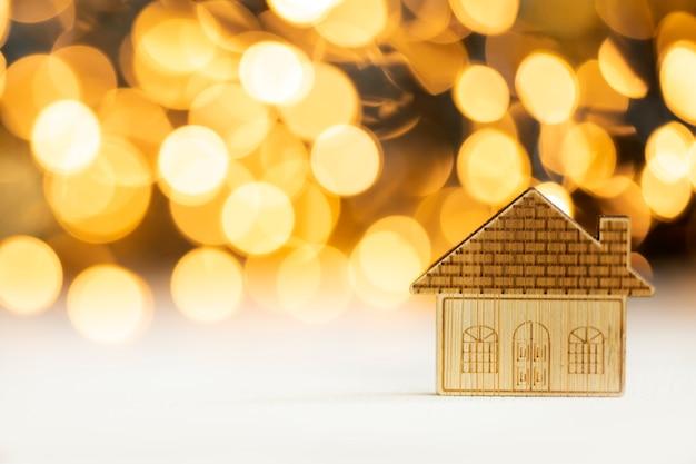 Kleines ikonenhaus mit goldglänzender bokeh-hintergrundinvestitionshypothek-immobilienkonzept